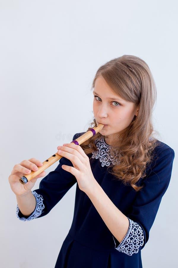 Menina que joga em uma flauta imagem de stock