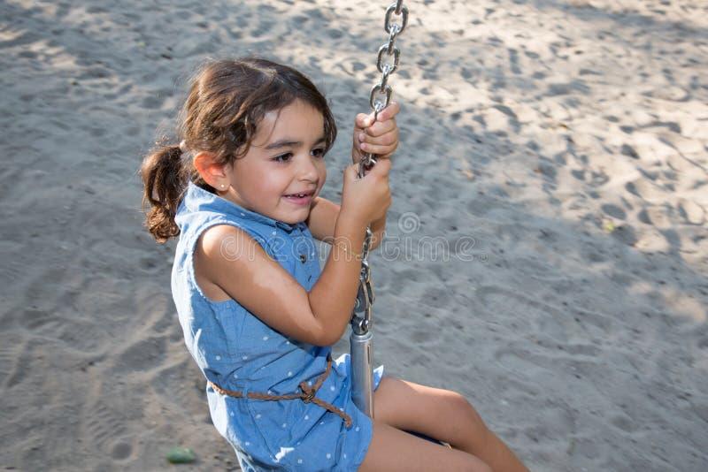 Menina que joga em uma linha do fecho de correr do campo de jogos das crianças com um sorriso feliz fotos de stock