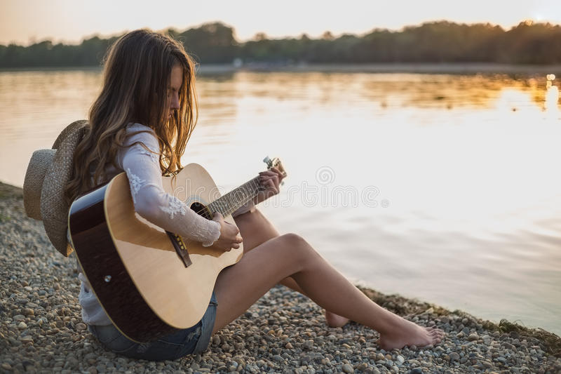 Menina que joga a guitarra ao sentar-se na praia imagem de stock