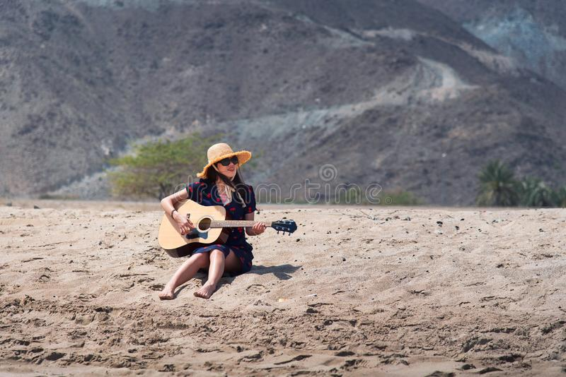Menina que joga a guitarra na praia imagem de stock royalty free