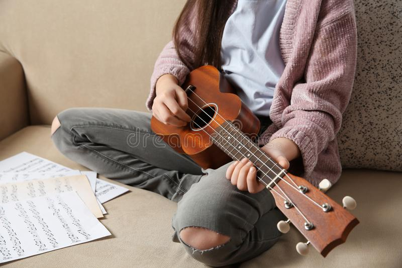Menina que joga a guitarra no sofá fotografia de stock