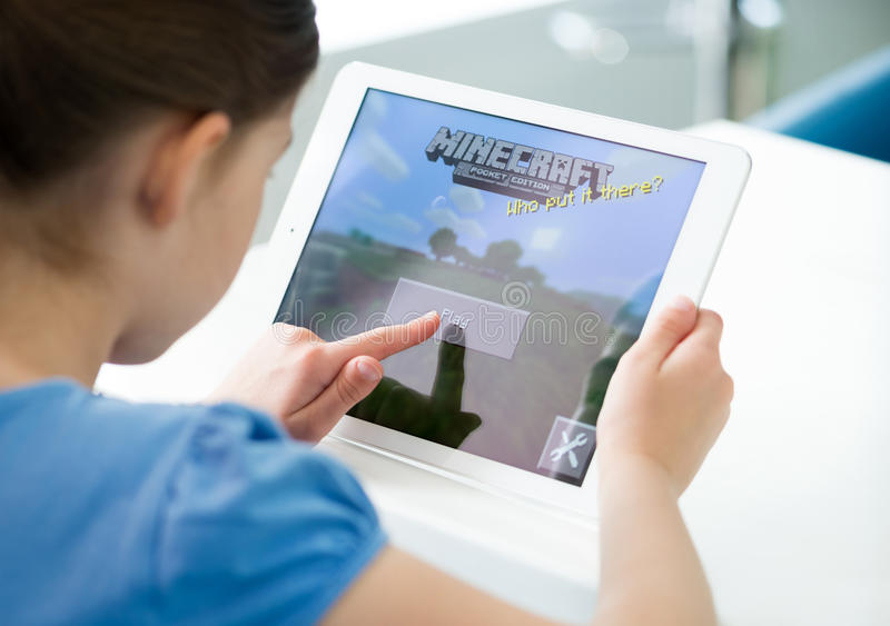 Menina que joga Minecraft no ar do iPad de Apple fotos de stock