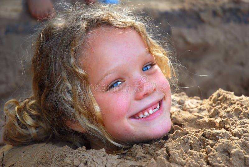 Menina que joga na areia imagem de stock