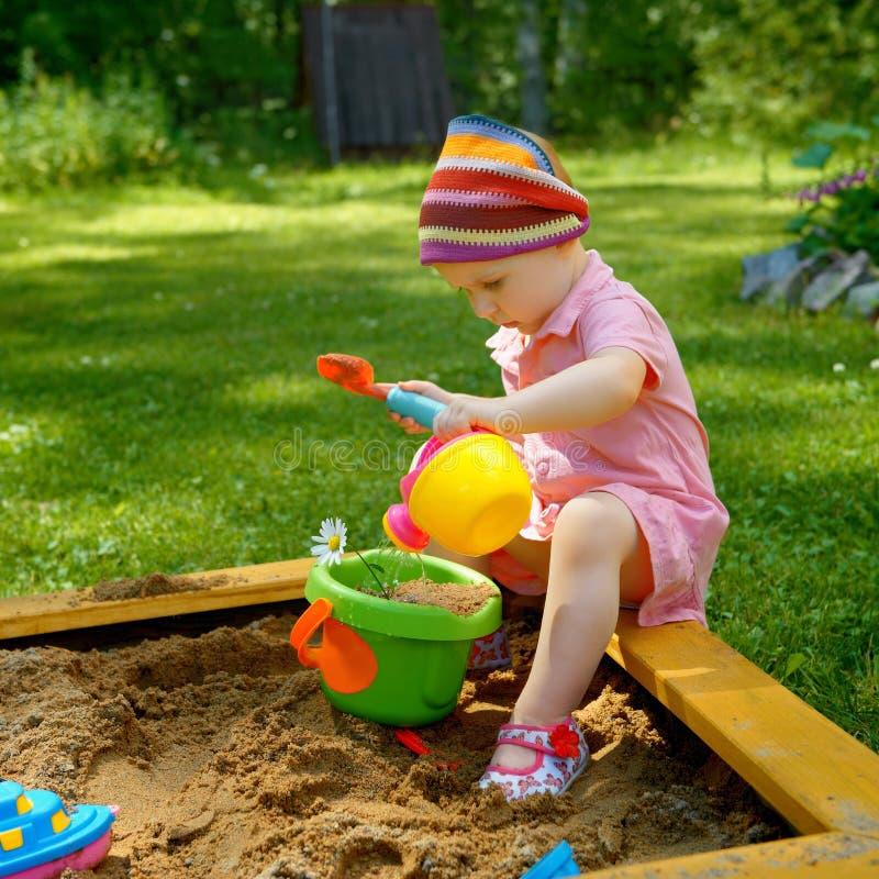 Menina que joga na caixa de areia imagem de stock royalty free