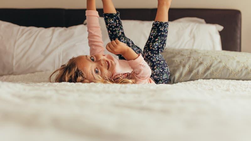 Menina que joga na cama fotografia de stock