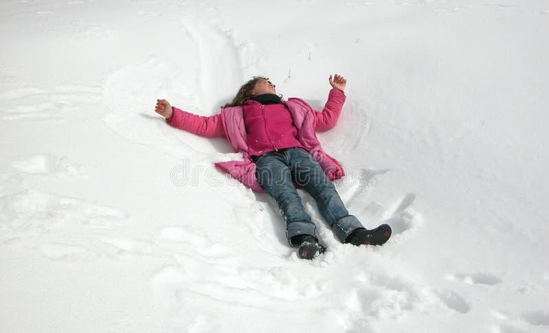 Menina que joga na neve durante o wintertime fotografia de stock