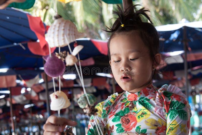 Menina que joga na praia com shell imagem de stock royalty free