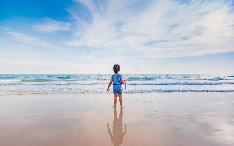Menina que joga na praia no por do sol fotos de stock