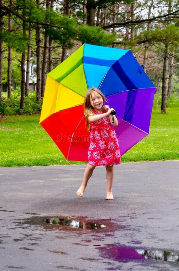 Menina que joga nas poças com guarda-chuva imagem de stock