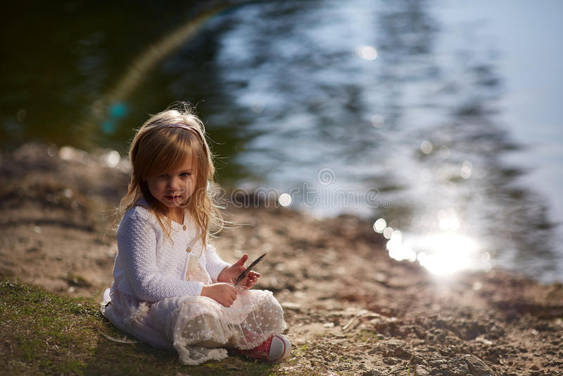 Menina que joga no banco de rio foto de stock royalty free
