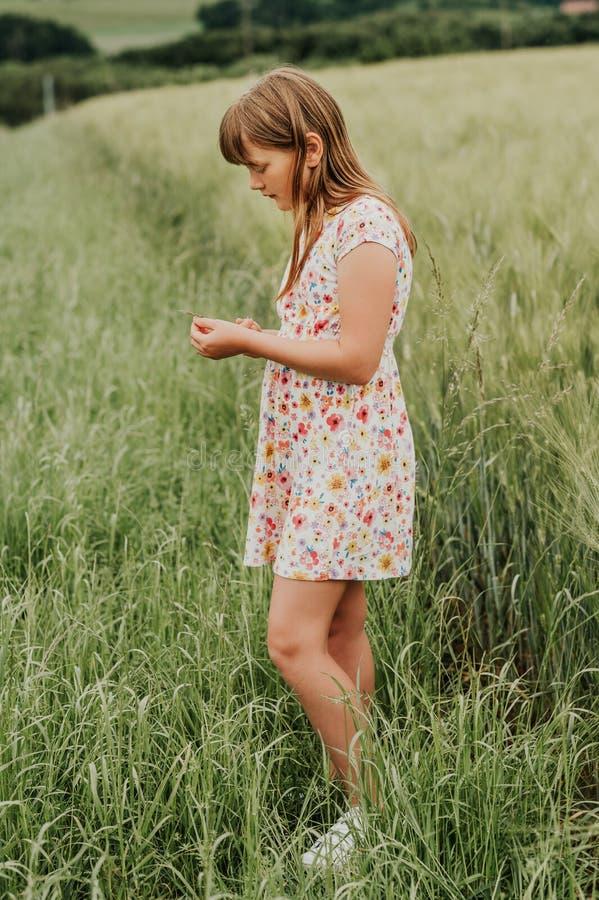 Menina que joga no campo de trigo verde no verão foto de stock