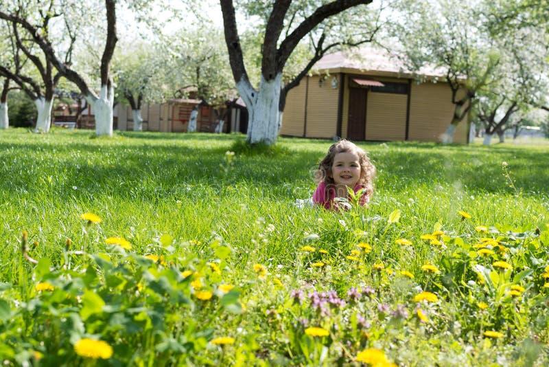 Menina que joga no gramado verde fotografia de stock