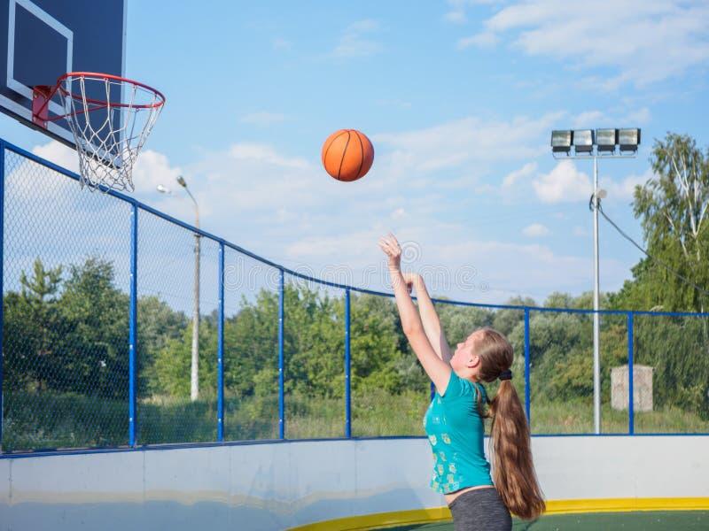 Menina que joga o basquetebol fora no dia de verão imagem de stock