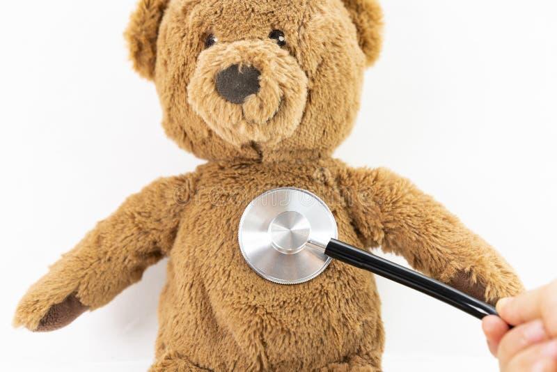 Menina que joga o doutor e o urso de peluche de escuta com o estetoscópio isolado no branco imagem de stock royalty free