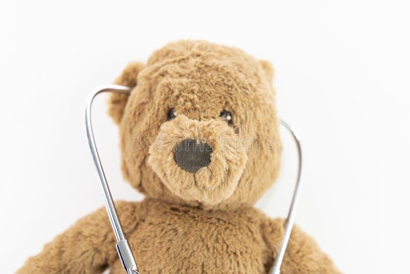 Menina que joga o doutor e o urso de peluche de escuta com o estetoscópio isolado no urso de WhiteTeddy e o estetoscópio em um fu fotografia de stock