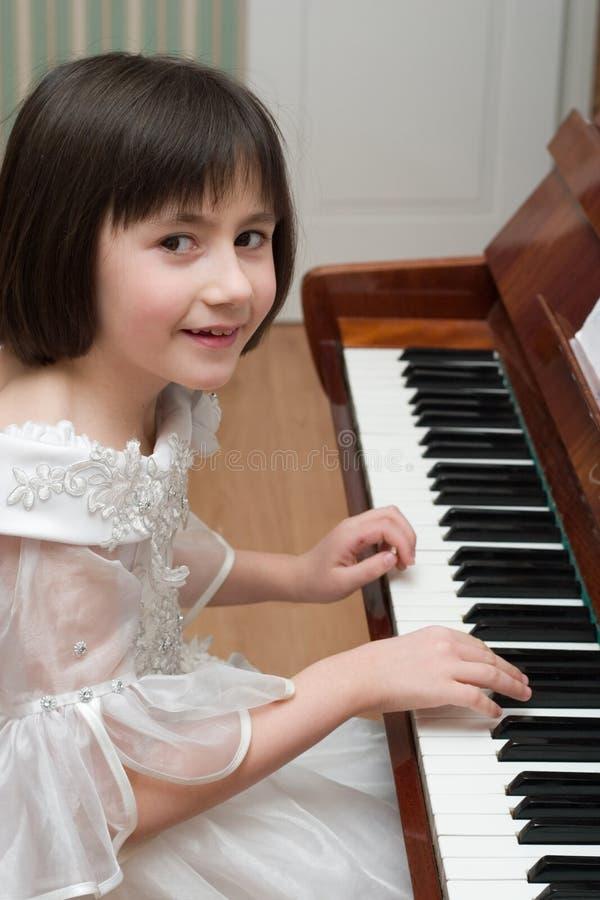 Menina que joga o piano imagem de stock