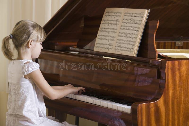 Menina que joga o piano imagens de stock