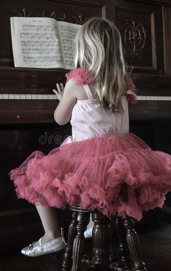 Menina que joga o piano fotografia de stock