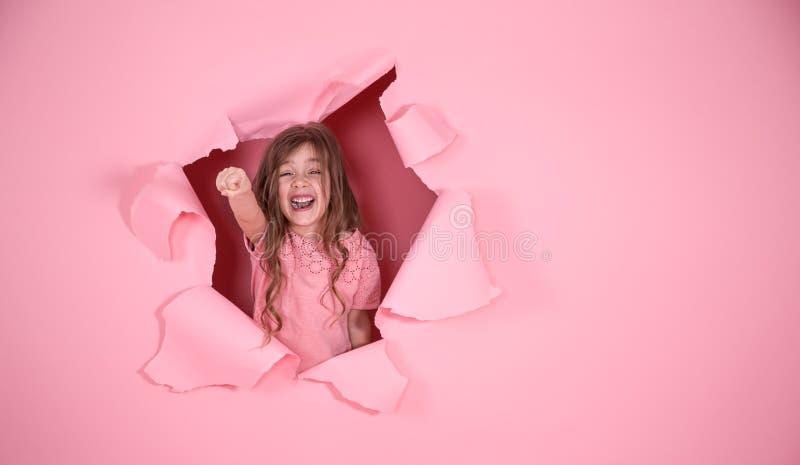 Menina que joga o super-herói no fundo cor-de-rosa imagem de stock