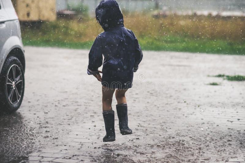 Menina que joga a parte externa sozinha no mau tempo foto de stock