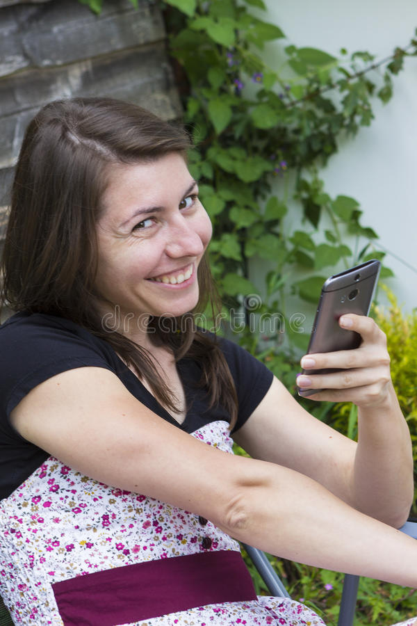 Menina que lê a mensagem móvel no telefone fotos de stock royalty free