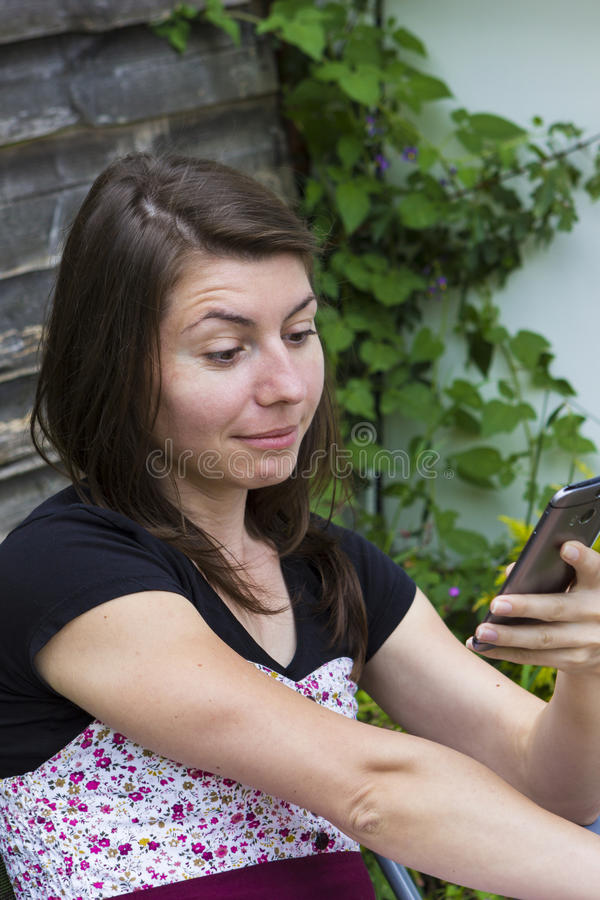 Menina que lê a mensagem móvel no telefone imagem de stock