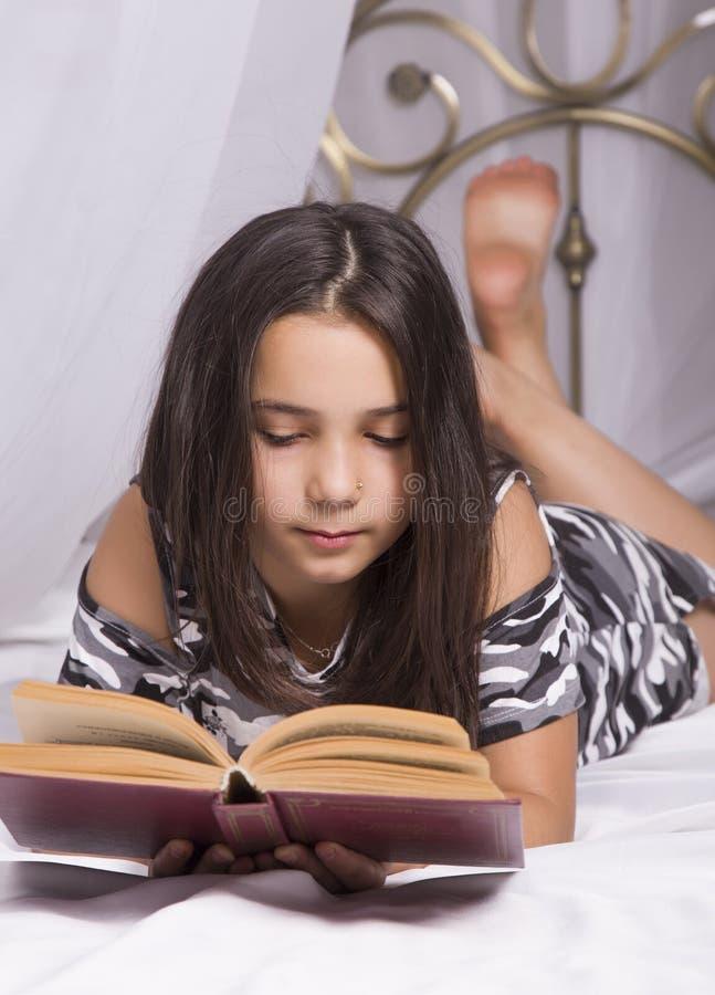 Menina que lê um livro que encontra-se na cama em sua sala educação home e estudo em casa imagem de stock royalty free