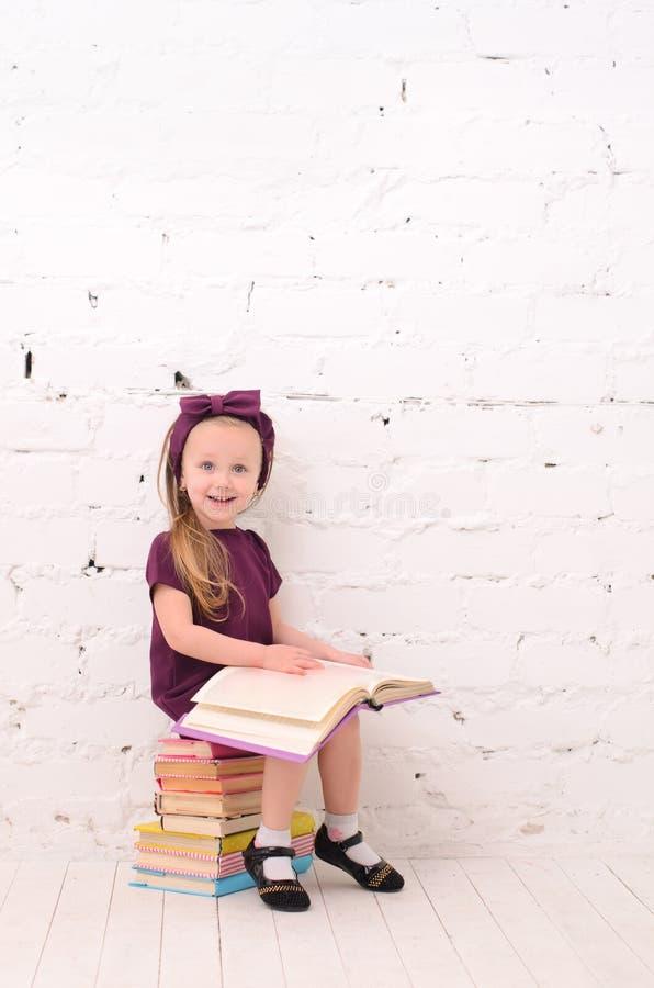 Menina que lê um livro, sentando-se em uma pilha dos livros imagem de stock