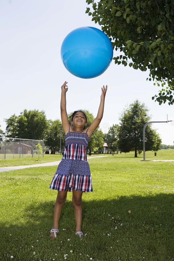 Menina que lanç acima da esfera fotografia de stock
