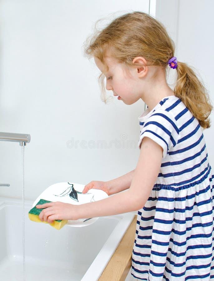 Menina que lava os pratos foto de stock royalty free