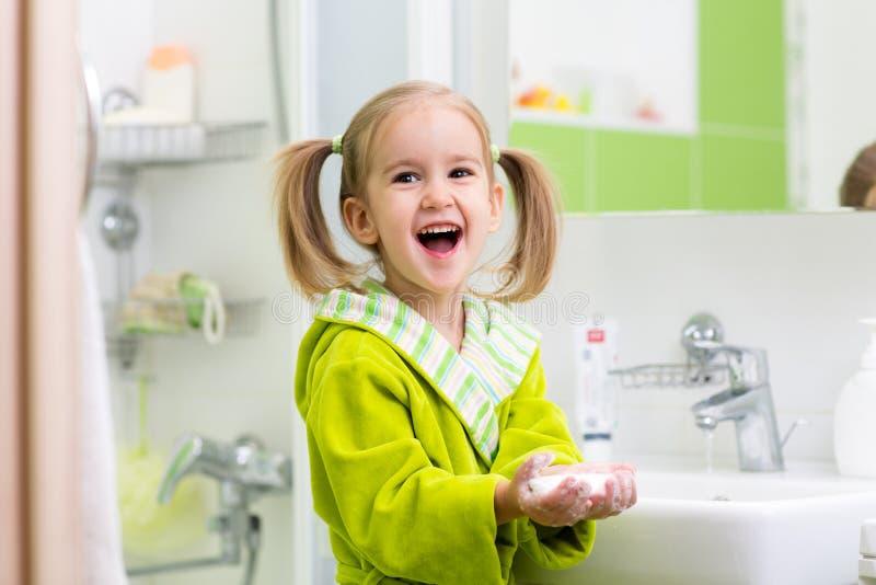 Menina que lava suas mãos no banheiro fotos de stock