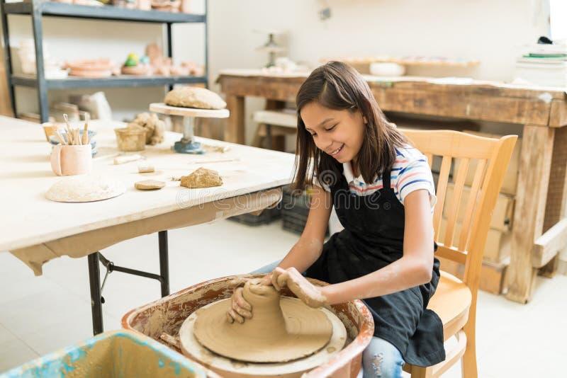 Menina que leva a cabo o passatempo da cerâmica na classe foto de stock