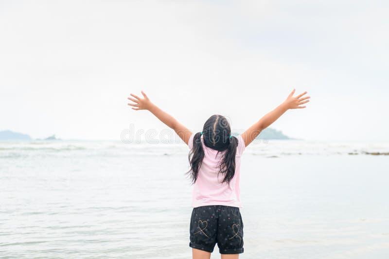Menina que levanta as mãos na praia, liberdade fotos de stock royalty free