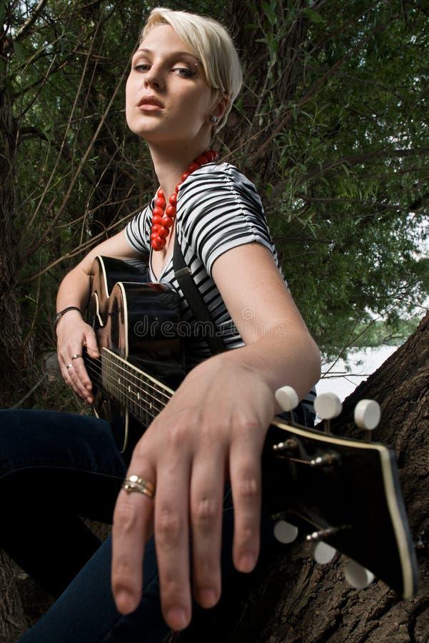 Menina que levanta com a guitarra nas madeiras imagem de stock royalty free