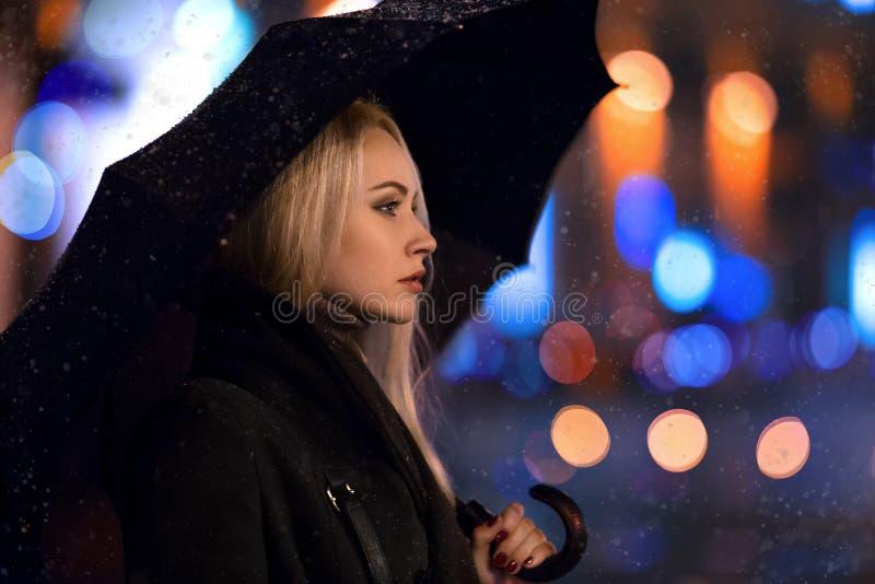 Menina que levanta com o guarda-chuva à vista de nivelar a cidade foto de stock