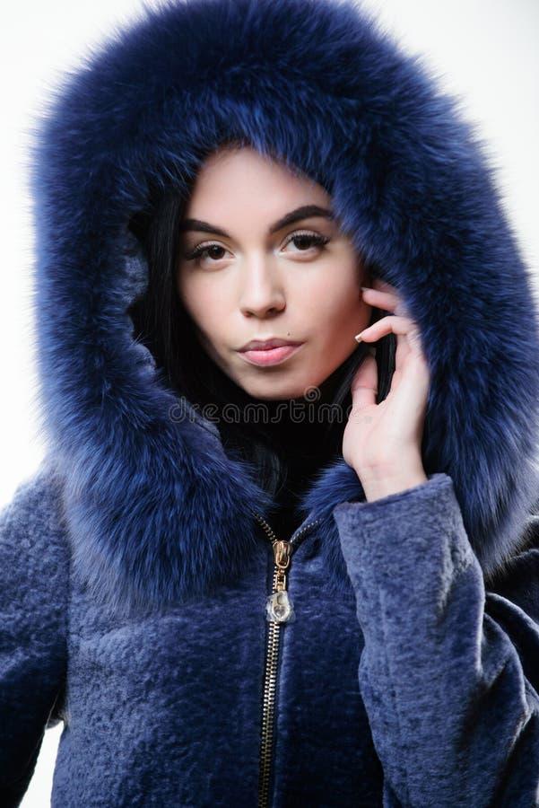 Menina que levanta o casaco de pele encapuçado Fêmea com obscuridade do desgaste da composição - casaco de pele macio azul Capa d imagem de stock royalty free