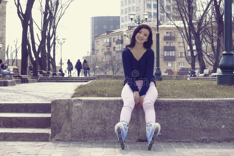 Menina que levanta patins de rolo vestindo fotos de stock royalty free