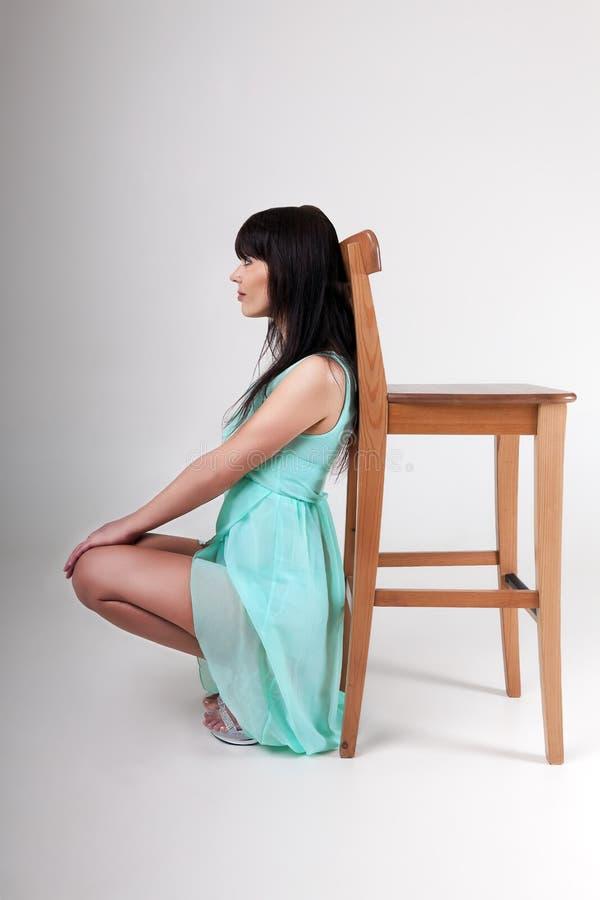 Menina que levanta perto da cadeira no estúdio foto de stock royalty free