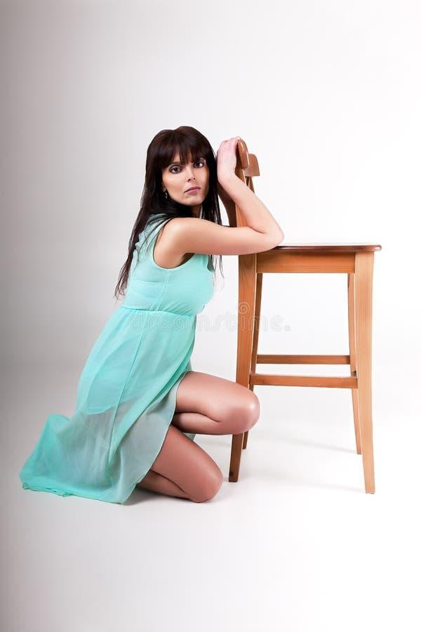 Menina que levanta perto da cadeira no estúdio fotografia de stock royalty free