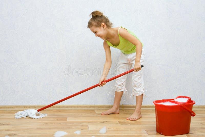 Menina que limpa o assoalho imagem de stock