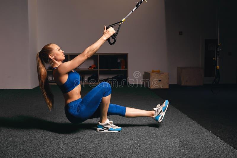 A menina que loura muscular fazer se senta levanta imagem de stock
