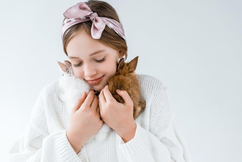 Menina que mantém coelhos peludos bonitos isolados no branco imagens de stock royalty free
