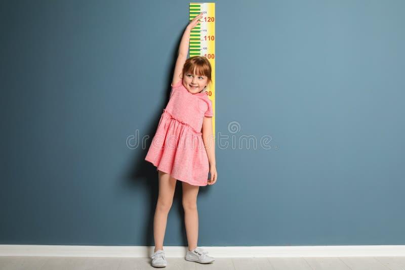 Menina que mede sua altura perto da parede fotos de stock royalty free