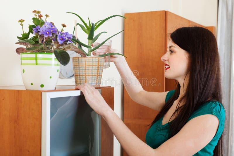 Menina que molha flores em pasta mim imagens de stock royalty free
