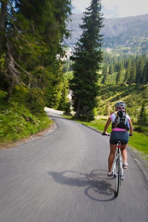 Menina que monta rapidamente na bicicleta. Borrão de movimento fotografia de stock royalty free