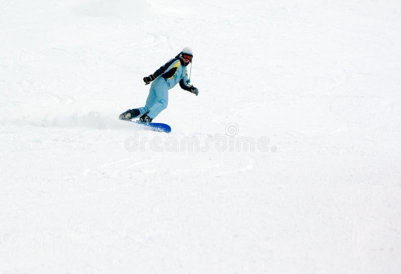 Menina que monta rapidamente no snowboard imagens de stock