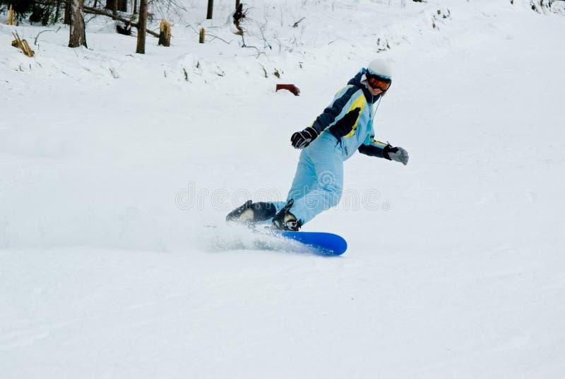 Menina que monta rapidamente no snowboard fotografia de stock royalty free