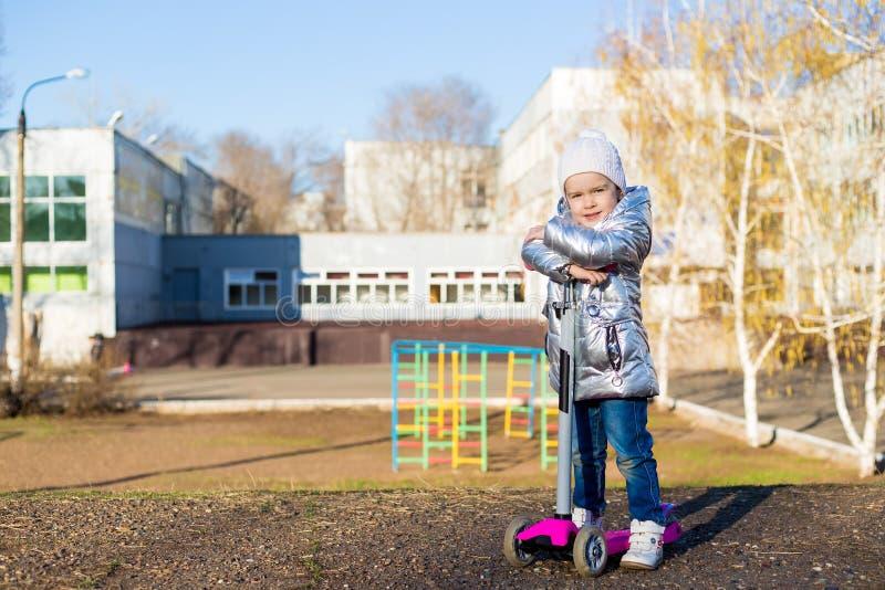 Menina que monta um 'trotinette' no parque em um dia de mola ensolarado Lazer ativo e esporte exterior para crian?as fotos de stock royalty free