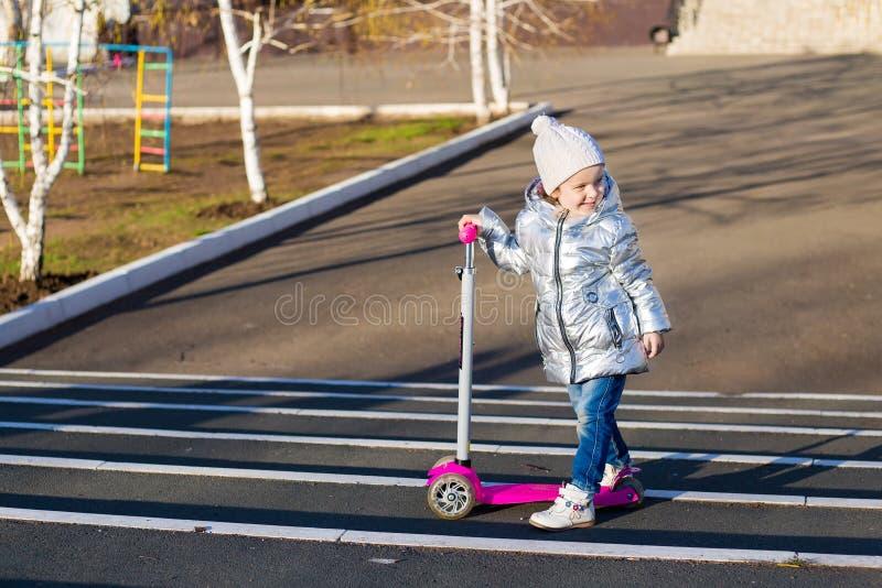 Menina que monta um 'trotinette' no parque em um dia de mola ensolarado Lazer ativo e esporte exterior para crian?as foto de stock