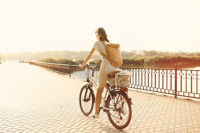 Menina que monta uma bicicleta no parque perto do lago fotografia de stock royalty free
